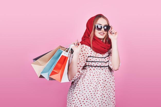 Portrait de jeune femme souriante heureuse avec des sacs à provisions sur le fond rose.