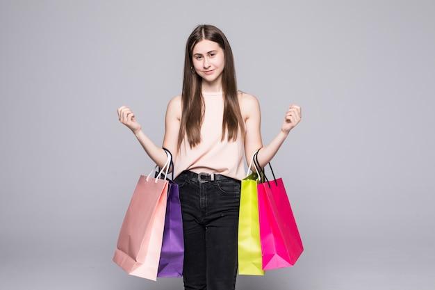 Portrait de jeune femme souriante heureuse avec des sacs à provisions sur mur blanc
