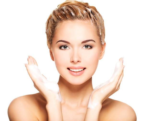 Portrait d'une jeune femme souriante lave ses cheveux sur un fond blanc
