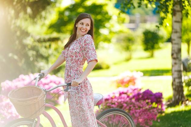 Portrait d'une jeune femme souriante en longue robe à fleurs rose s'arrêtant pour faire du vélo vintage avec panier pour les achats sur fond de fleurs à l'extérieur. temps de récréation assez féminin au printemps, parc d'été