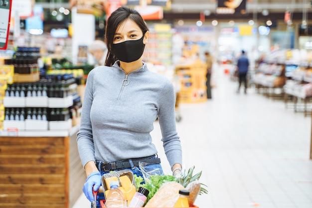 Portrait d'une jeune femme souriante en masque de protection et gants tenant un panier d'épicerie dans un supermarché.