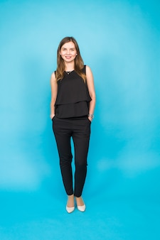 Portrait de jeune femme souriante sur mur bleu