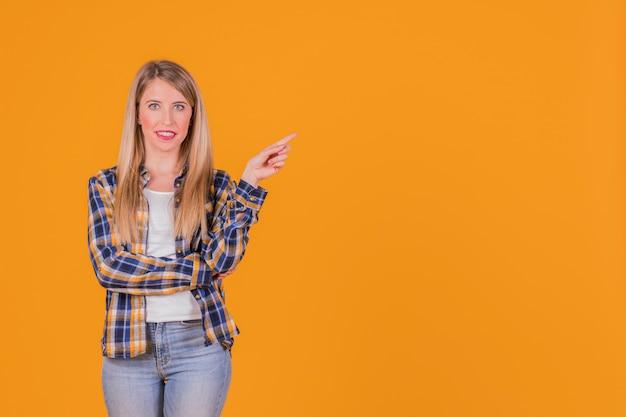 Portrait d'une jeune femme souriante, pointant son doigt sur un fond orange