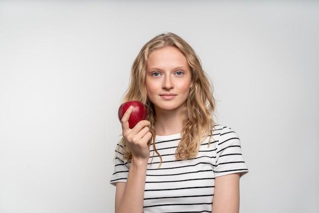 Portrait de jeune femme souriante avec pomme rouge. visage frais, beauté naturelle, réaliste. nettoyez la peau jeune et fraîche sans maquillage ni retouche.