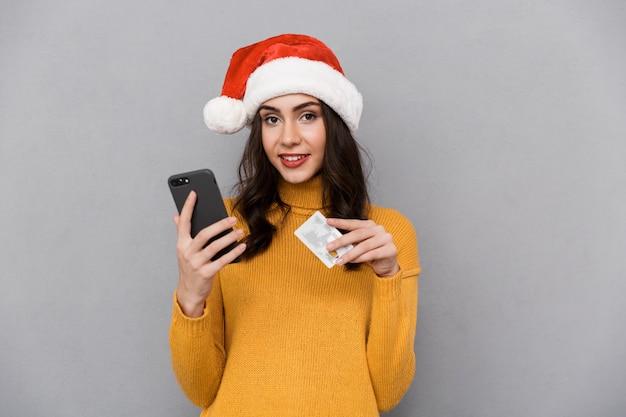 Portrait d'une jeune femme souriante portant chapeau de père noël rouge debout isolé sur fond gris, à l'aide de téléphone mobile, montrant une carte de crédit en plastique