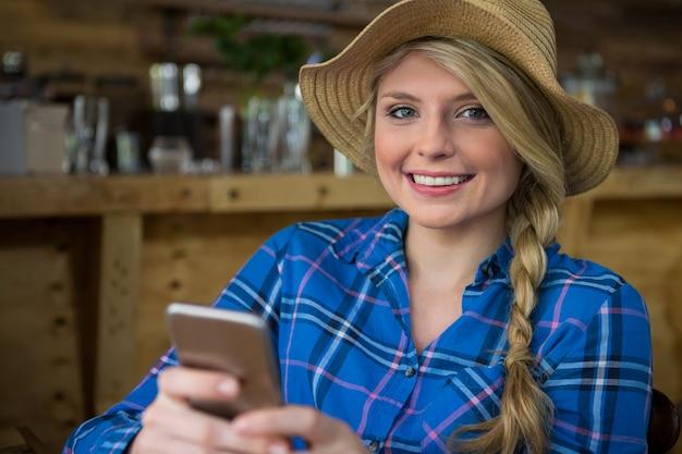 Portrait de jeune femme souriante portant un chapeau tout en utilisant un téléphone mobile dans un café