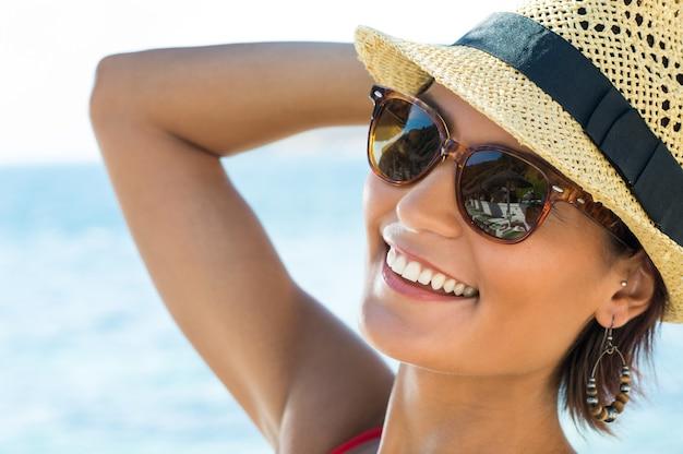 Portrait de jeune femme souriante portant des lunettes de soleil