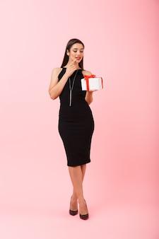 Portrait d'une jeune femme souriante portant une robe noire debout isolé sur fond rose, tenant une boîte-cadeau
