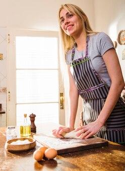 Portrait, de, a, jeune femme souriante, porter, tablier, pétrir la pâte, sur, planche planche