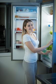 Portrait de jeune femme souriante posant au réfrigérateur ouvert en fin de soirée