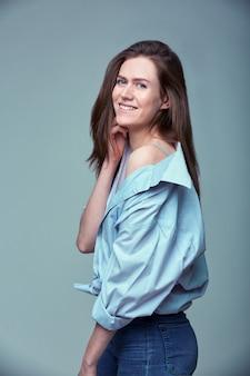 Portrait d'une jeune femme souriante posant sur fond gris, espace copie