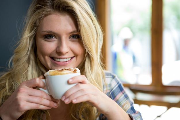 Portrait de jeune femme souriante prenant un café au café