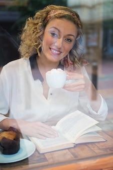 Portrait de jeune femme souriante prenant un café tout en lisant un livre vu à travers la fenêtre du café