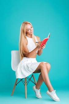 Portrait d'une jeune femme souriante prenant des notes assise sur une chaise isolée sur fond bleu
