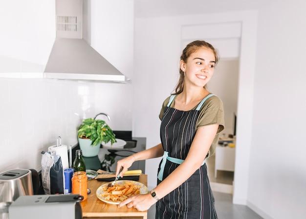 Portrait de jeune femme souriante préparant des pâtes dans la cuisine