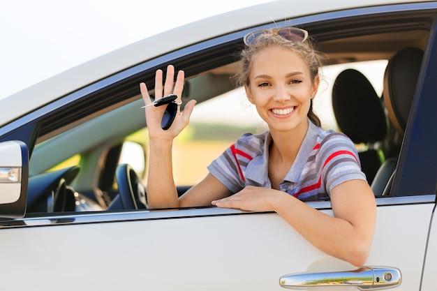 Portrait de jeune femme souriante regardant par la fenêtre de sa voiture montrant la clé de voiture