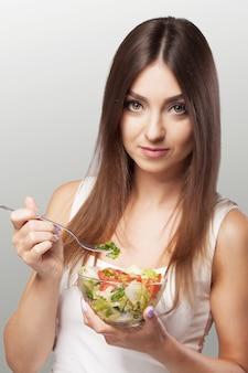 Portrait d'une jeune femme souriante avec une salade de légumes végétariens.