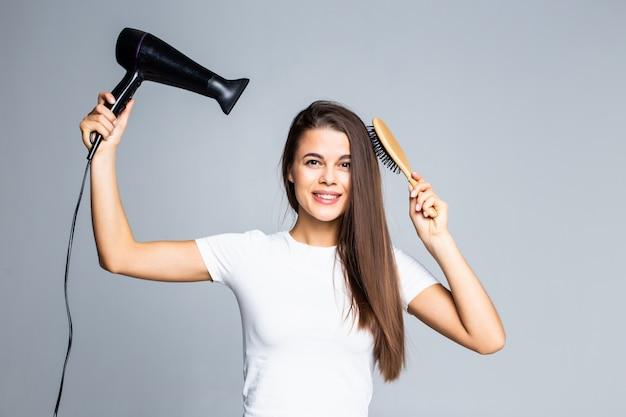 Portrait d'une jeune femme souriante sèche ses cheveux sur fond gris