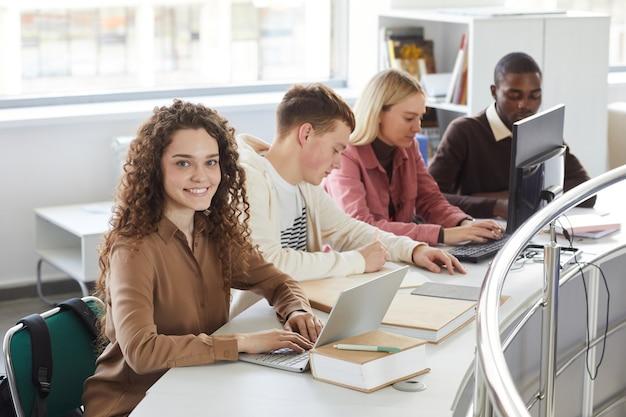 Portrait de jeune femme souriante et souriant tout en étudiant avec un groupe d'étudiants dans la bibliothèque du collège