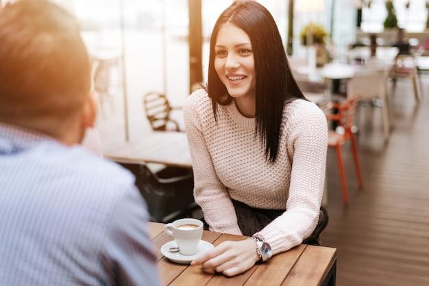 Portrait de jeune femme souriante à une table de café parler avec un ami.