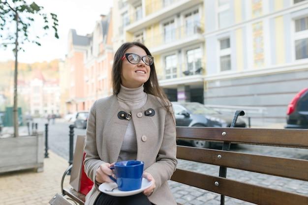 Portrait de jeune femme souriante avec une tasse de thé assis sur un banc