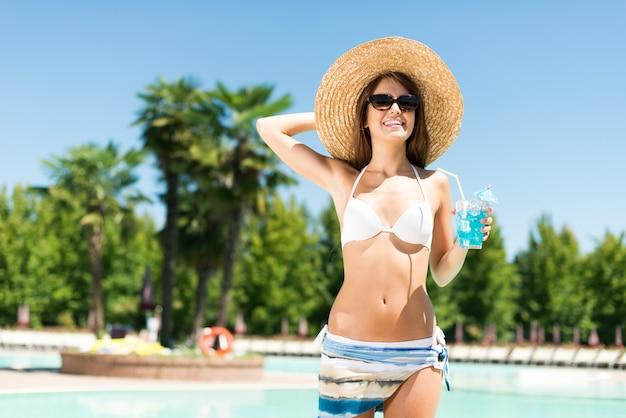 Portrait d'une jeune femme souriante tenant un cocktail pendant les vacances