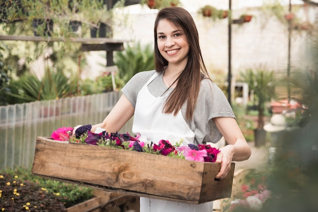 Portrait d'une jeune femme souriante tenant des pétunias colorés dans une caisse en bois