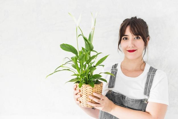 Portrait d'une jeune femme souriante tenant une plante en pot
