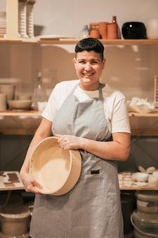 Portrait d'une jeune femme souriante tenant un récipient en céramique dans la main