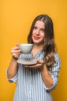 Portrait d'une jeune femme souriante tenant une soucoupe et une tasse dans les mains