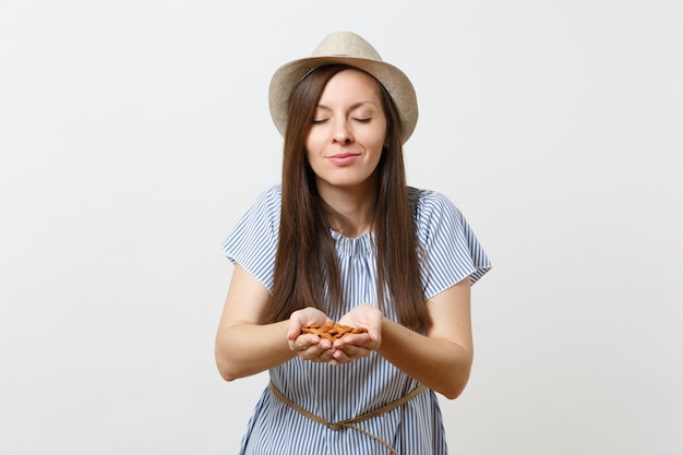 Portrait de jeune femme souriante tenir dans les mains des noix d'amandes non transformées brunes isolées sur fond blanc. une bonne nutrition, une alimentation végétarienne végétalienne, un concept de régime alimentaire sain. espace de copie