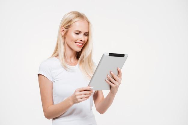 Portrait d'une jeune femme souriante travaillant sur tablette