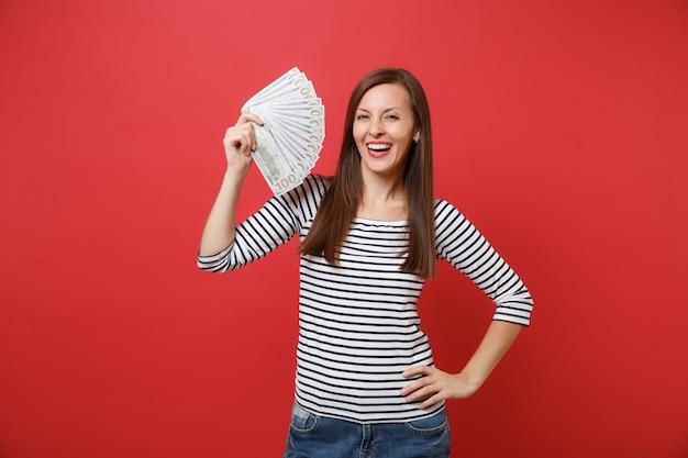 Portrait de jeune femme souriante en vêtements rayés tenant beaucoup de dollars, argent comptant isolé sur fond de mur rouge vif. les gens émotions sincères, concept de style de vie. maquette de l'espace de copie.