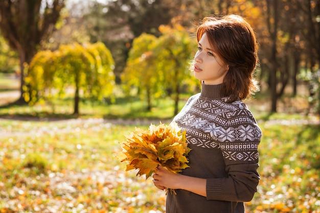 Portrait, jeune, femme, sourire, automne, parc, feuilles