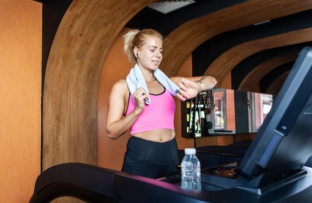 Portrait D'une Jeune Femme Sportive Joyeuse Avec Une Serviette Sur Les épaules Sur Un Tapis Roulant Photo Premium