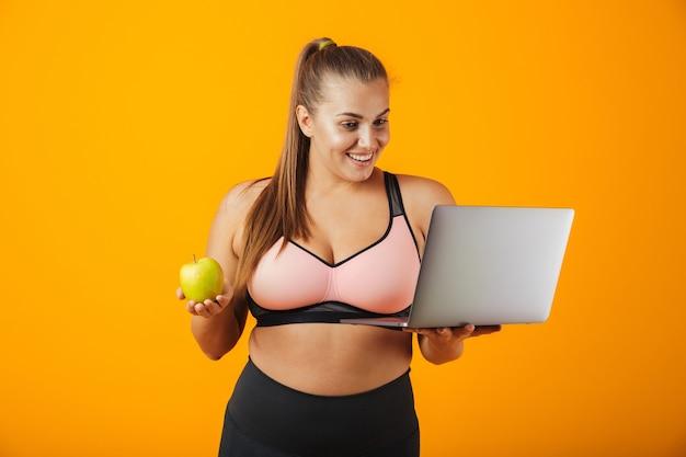 Portrait d'une jeune femme en surpoids heureux portant des vêtements de sport debout isolé sur un mur jaune, à l'aide d'un ordinateur portable, tenant une pomme verte