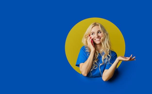 Portrait de jeune femme surprise debout sur un mur bleu. femme peep hors d'un trou dans le mur. espace vide pour le texte.