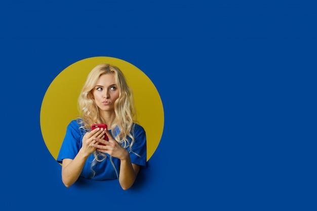 Portrait de jeune femme surprise debout sur un mur bleu. femme peep hors d'un trou dans le mur.