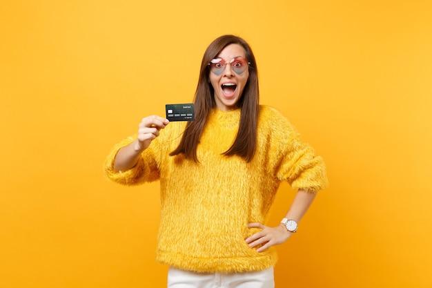 Portrait d'une jeune femme surprise excitée en pull de fourrure et lunettes coeur tenant une carte de crédit isolée sur fond jaune vif. les gens émotions sincères, concept de style de vie. espace publicitaire.