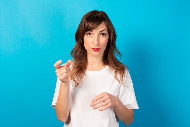 Portrait d'une jeune femme sympathique en t-shirt décontracté sur bleu. visage émotionnel