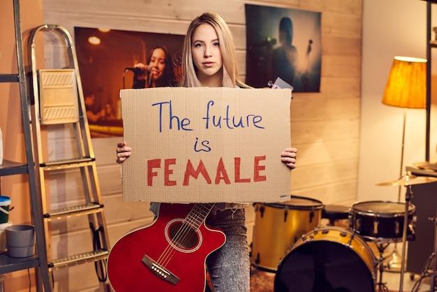 Portrait de jeune femme tenant une affiche et regardant la caméra en se tenant debout dans un studio de musique