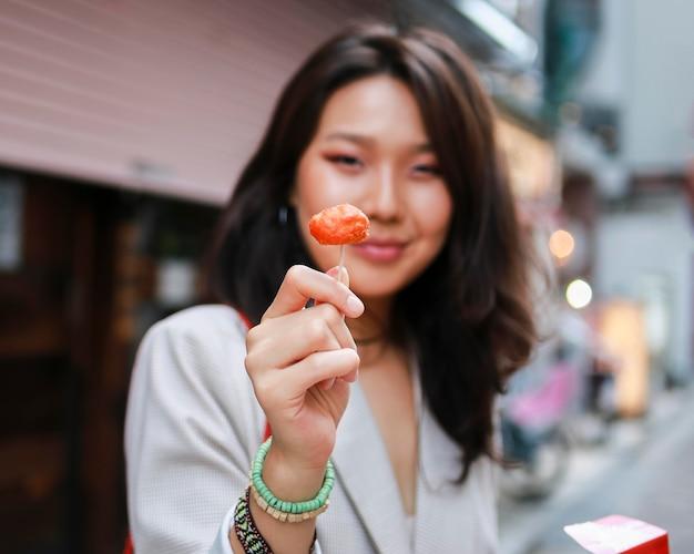 Portrait de jeune femme tenant des bonbons