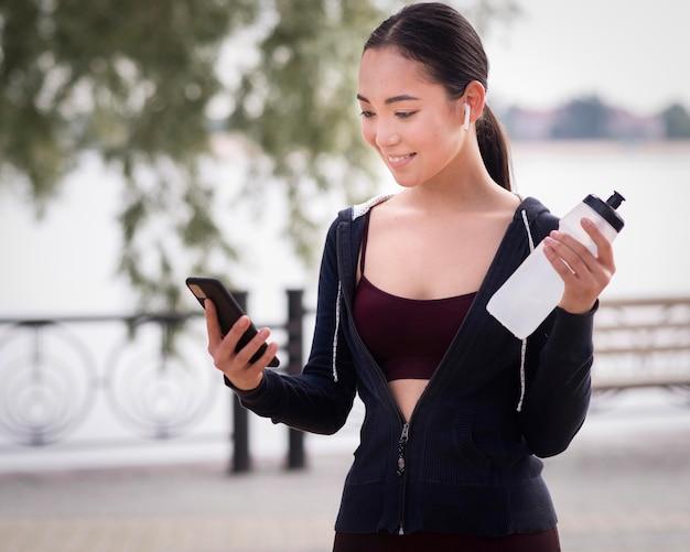 Portrait de jeune femme tenant une bouteille d'eau