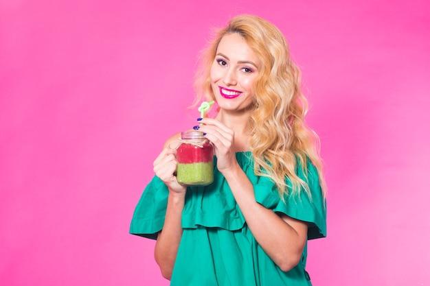 Portrait de jeune femme tenant et buvant un délicieux milk-shake smoothie vert sur un mur rose.