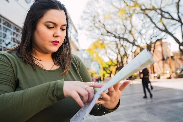 Portrait de jeune femme tenant une carte et à la recherche de directions à l'extérieur dans la rue