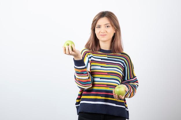Portrait d'une jeune femme tenant deux pommes vertes fraîches.