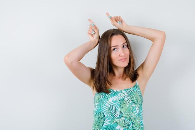 Portrait de jeune femme tenant les doigts au-dessus de la tête comme des cornes en chemisier et à la jolie vue de face