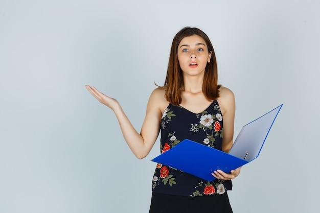 Portrait de jeune femme tenant un dossier tout en montrant un geste impuissant en blouse, jupe et regardant perplexe vue de face