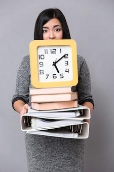 Portrait d'une jeune femme tenant des livres, des dossiers et une horloge murale sur mur gris
