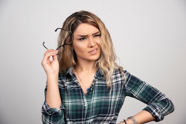 Portrait de jeune femme tenant des lunettes.
